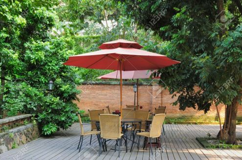 4093785-Summer-Patio-with-tables-and-cane-chairs-under-umbrella-in-China-Stock-Photo